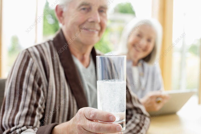 Older man taking medication in water