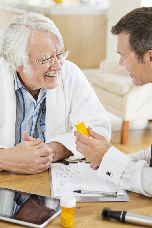 Doctor giving medication to older patient