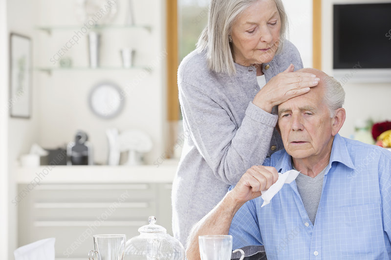 Woman feeling sick husband's forehead