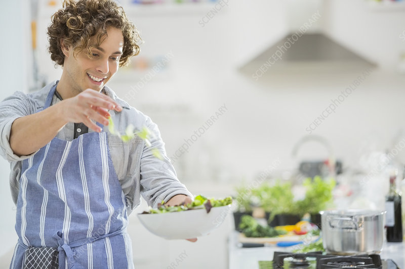 Man making salad in kitchen