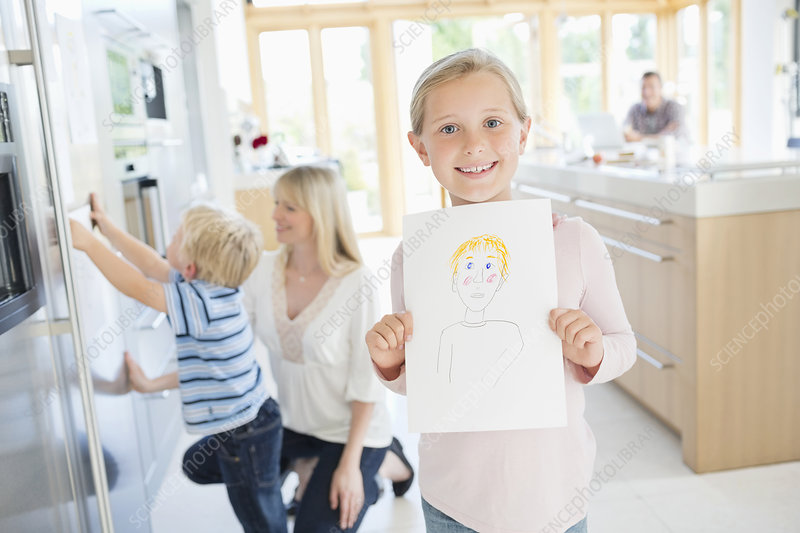 Girl showing off drawing in kitchen