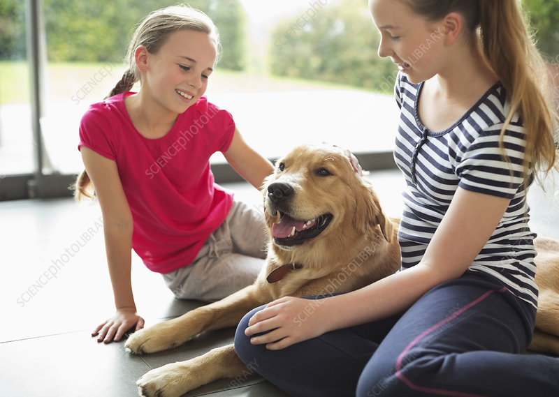 Girls relaxing with dog in living room