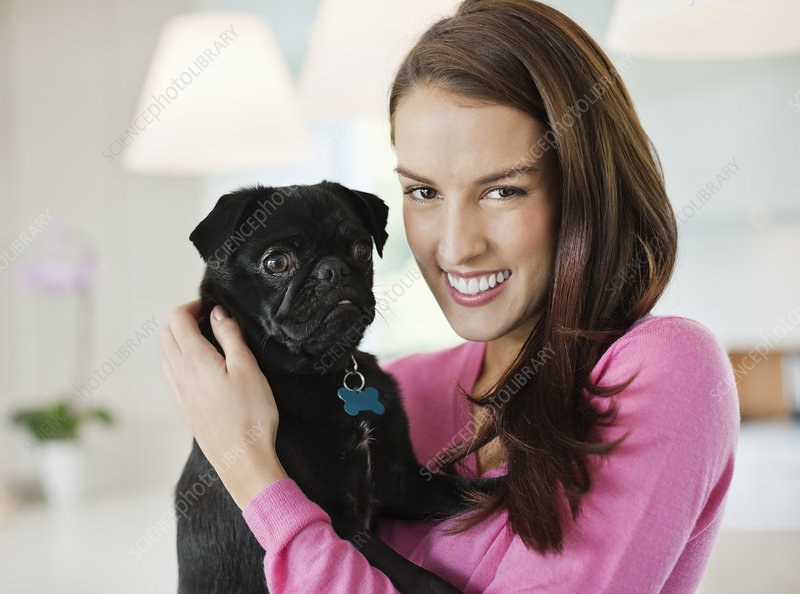 Smiling woman holding dog indoors