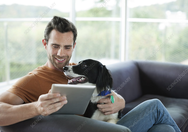 Man petting dog and using tablet computer