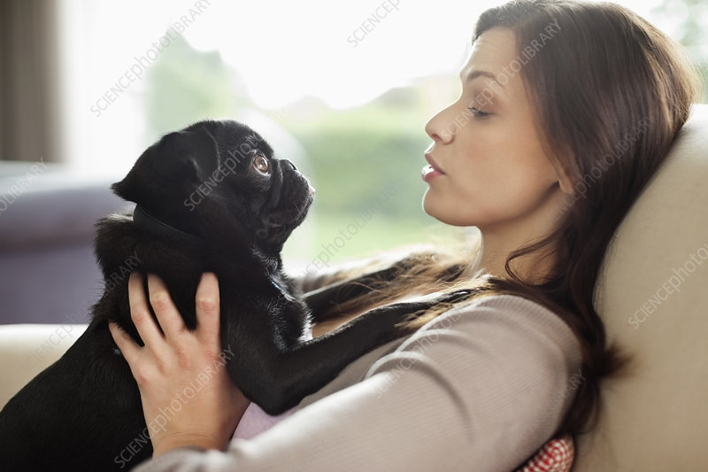 Woman relaxing with dog on sofa