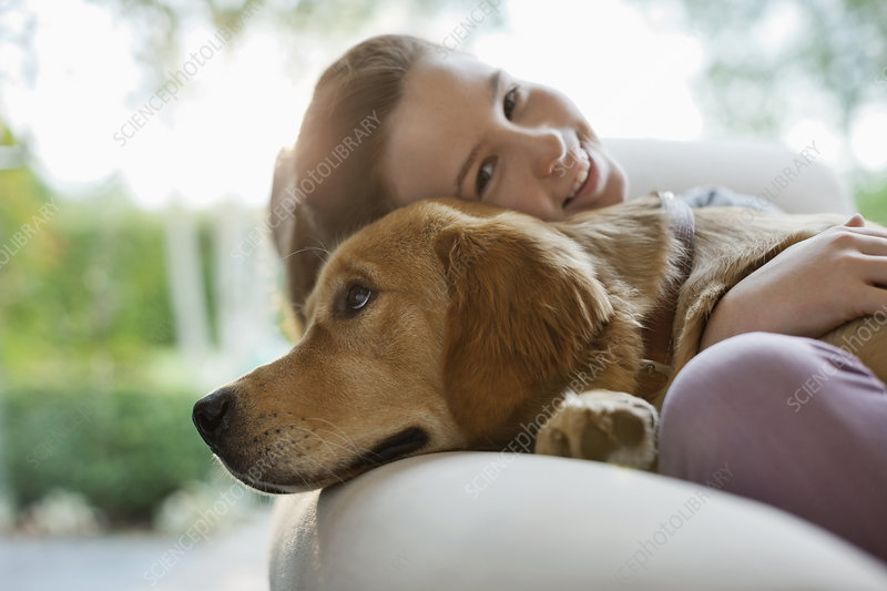 Girl relaxing with dog on sofa