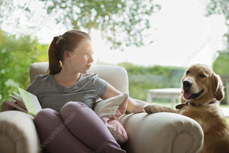 Girl relaxing with dog in armchair