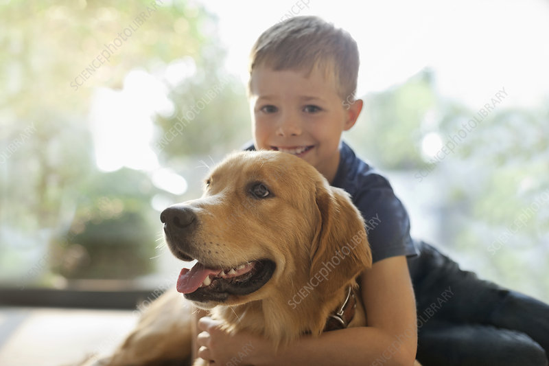 Smiling boy hugging dog indoors