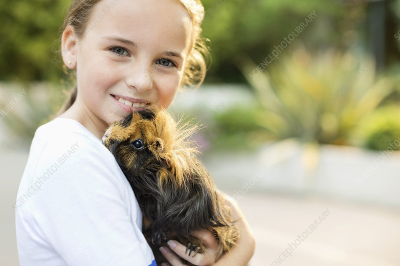 Smiling girl holding guinea pig outdoors