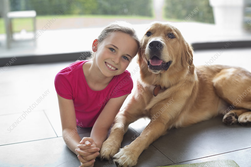 Smiling girl relaxing with dog indoors