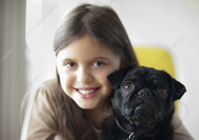 Smiling girl holding dog