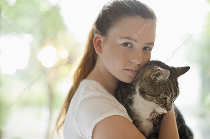 Girl holding cat indoors