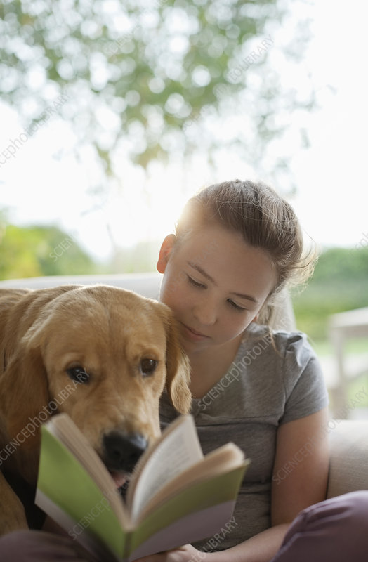 Girl reading with dog in armchair