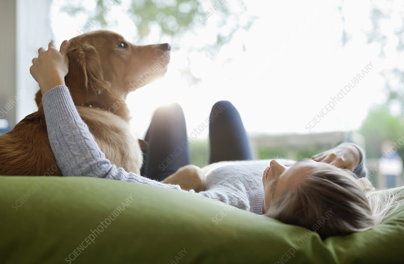 Woman petting dog on bed