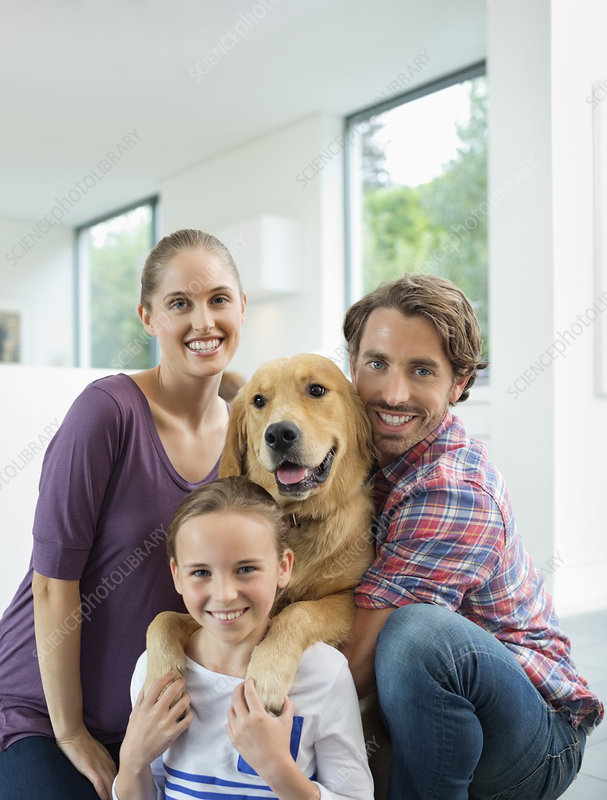 Family smiling with dog indoors