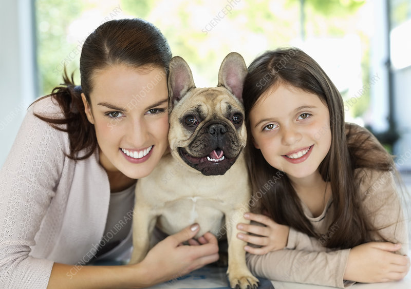 Smiling mother and daughter hugging dog