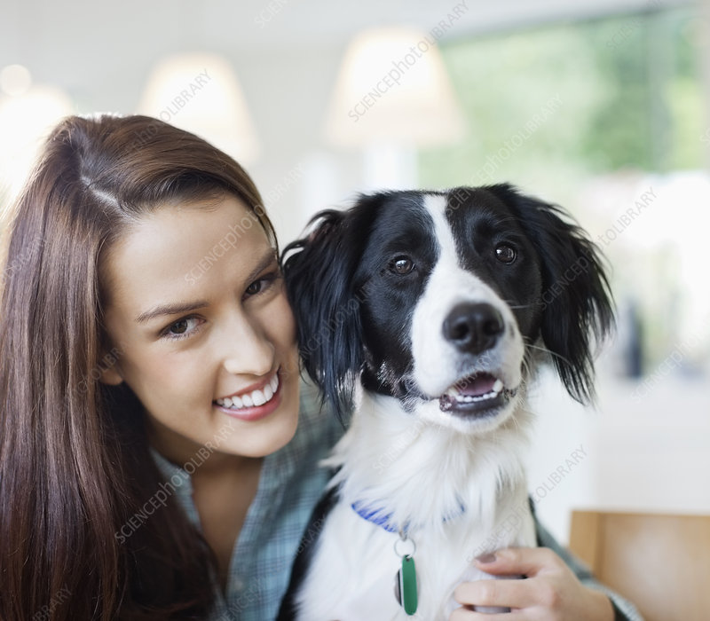 Smiling woman hugging dog indoors