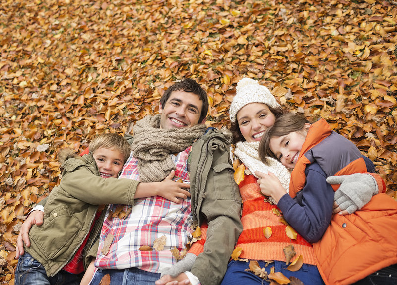 Smiling family laying in autumn leaves