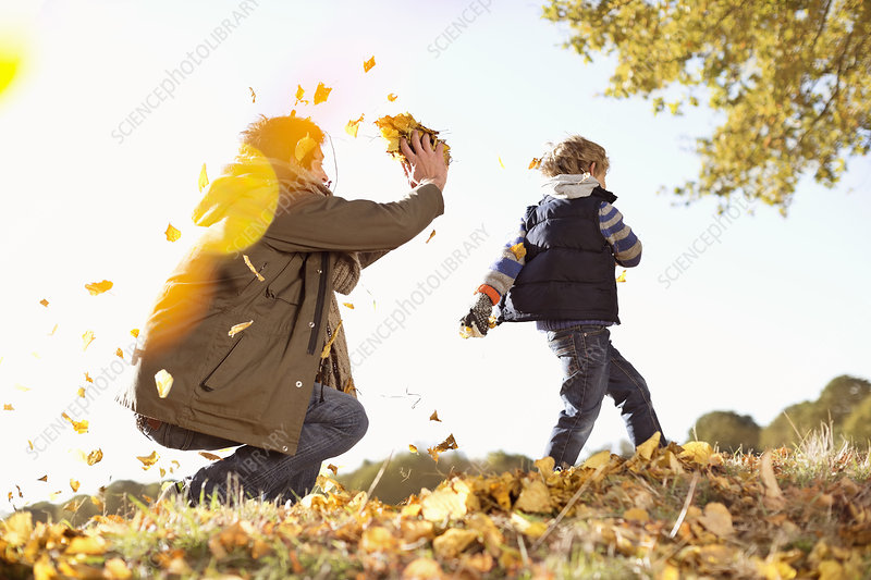 Father and son playing in autumn leaves