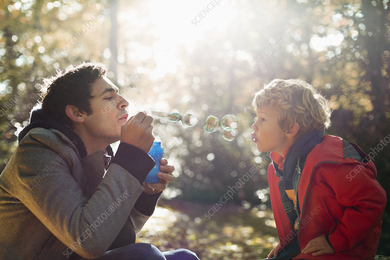 Father and son blowing bubbles in park