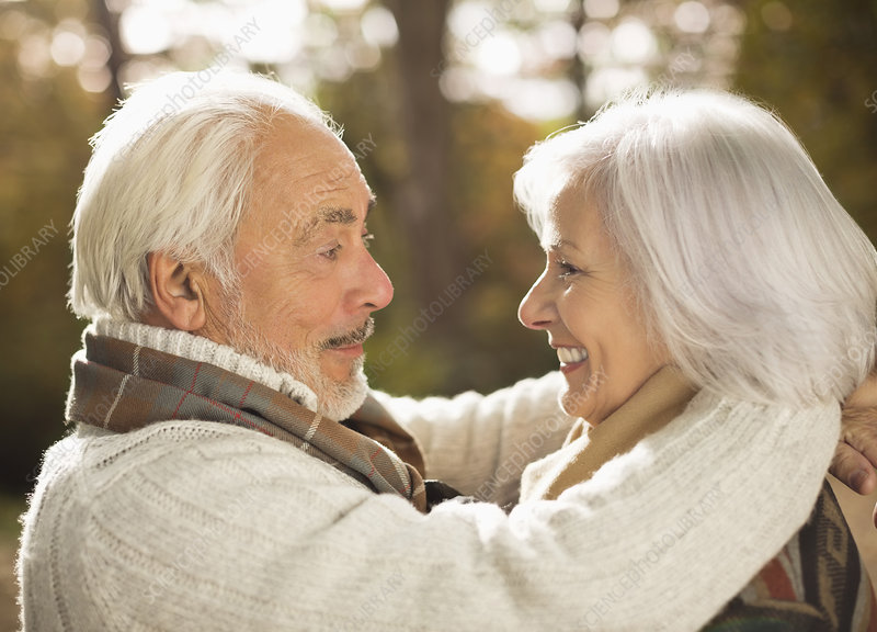 Older couple hugging outdoors