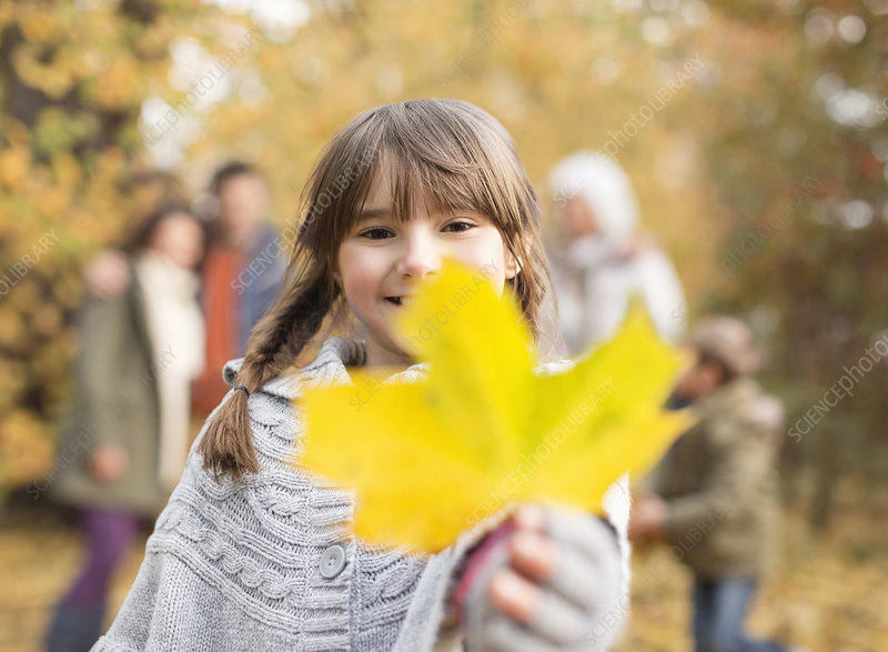 Girl holding autumn leaf in park