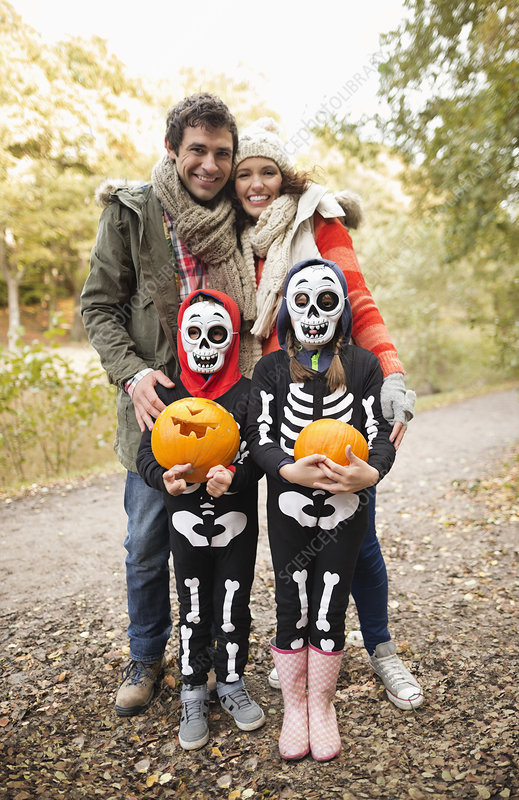 Couple with children in skeleton costumes