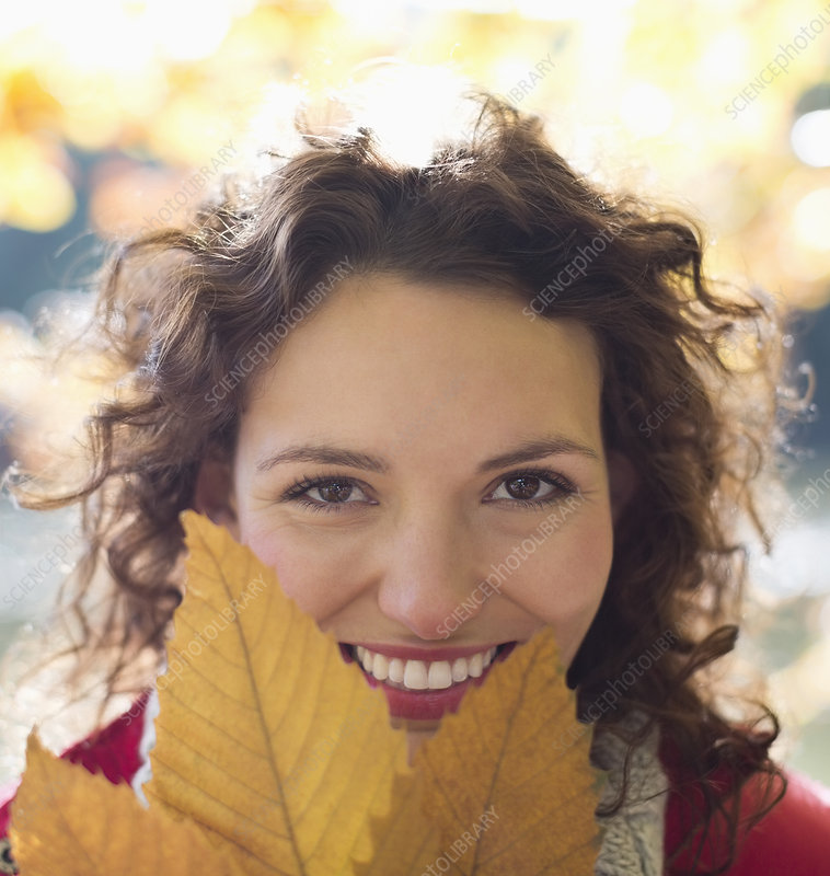 Smiling woman holding autumn leaf