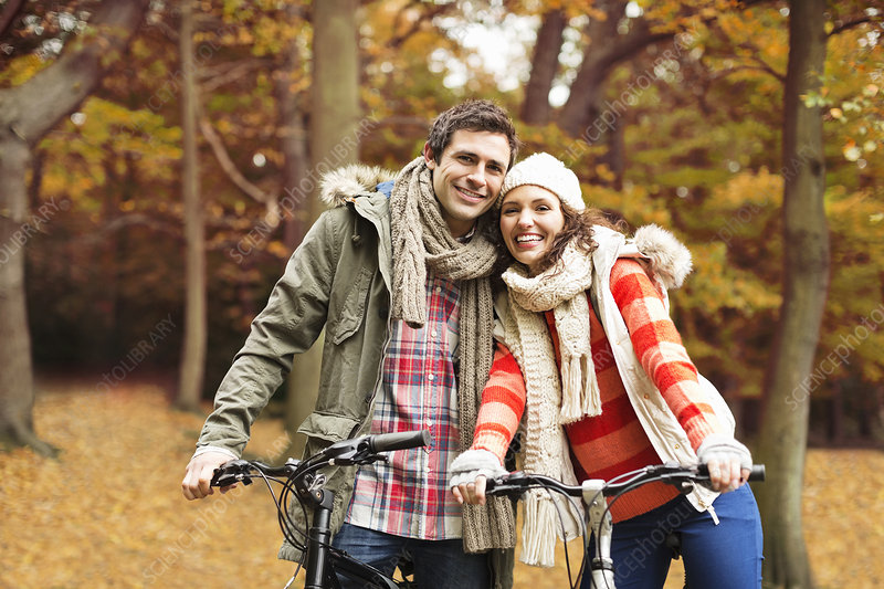 Couple riding bicycles together in park