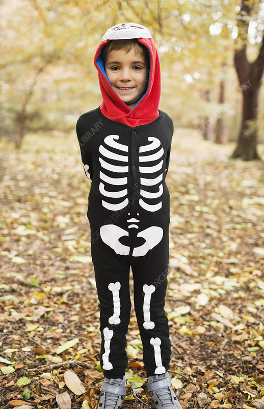 Boy wearing skeleton costume in park