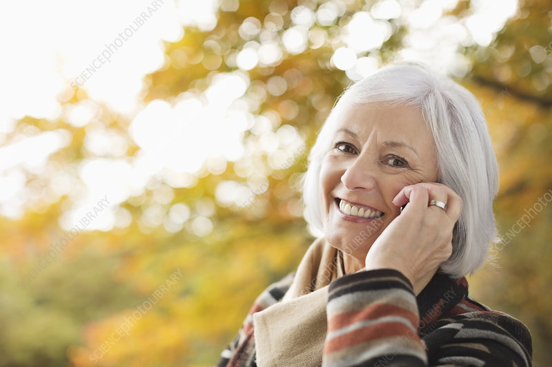 Older woman talking on cell phone in park
