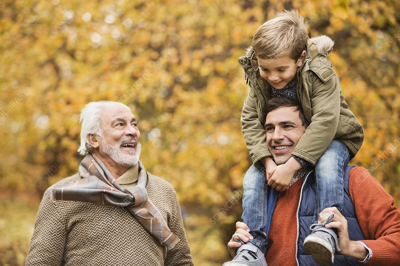 Three generations of men smiling in park