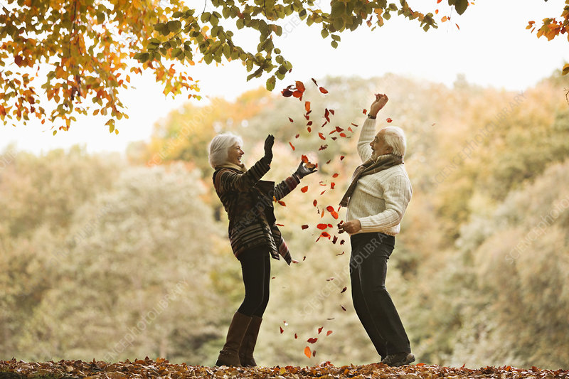 Older couple playing in autumn leaves