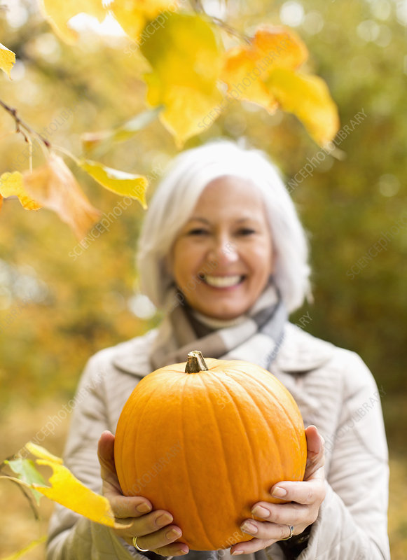 Older woman holding pumpkin in park