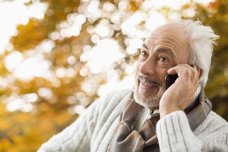 Older man talking on cell phone in park