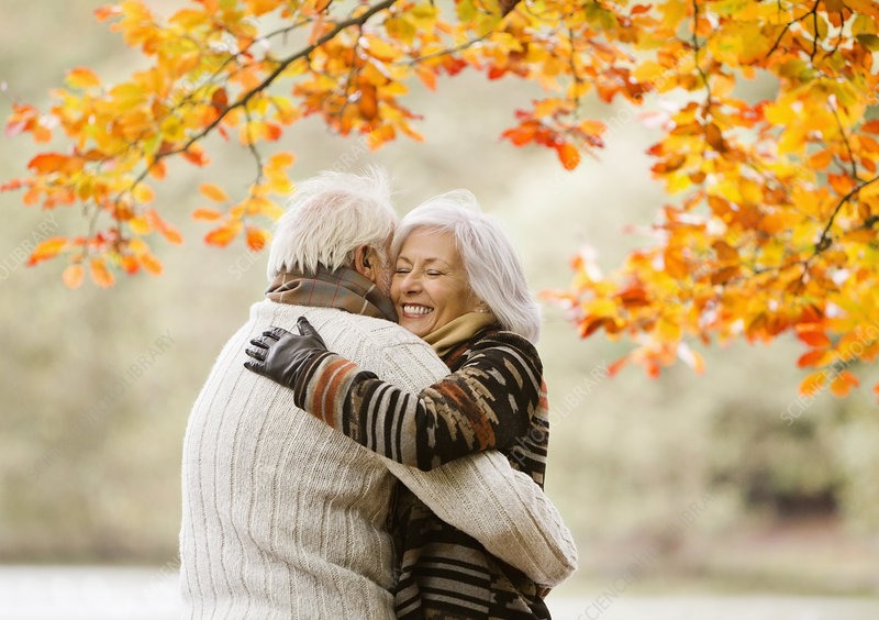 Older couple hugging in park