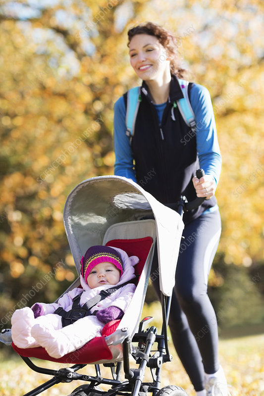 Woman running with baby stroller in park