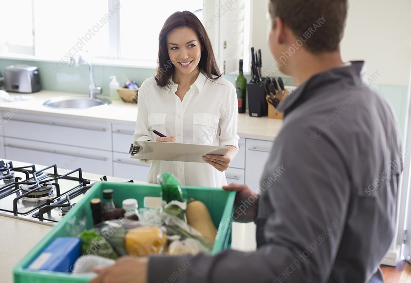 Woman signing for delivery in kitchen