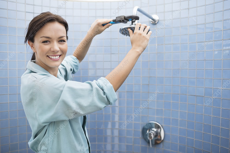 Female plumber working on shower head