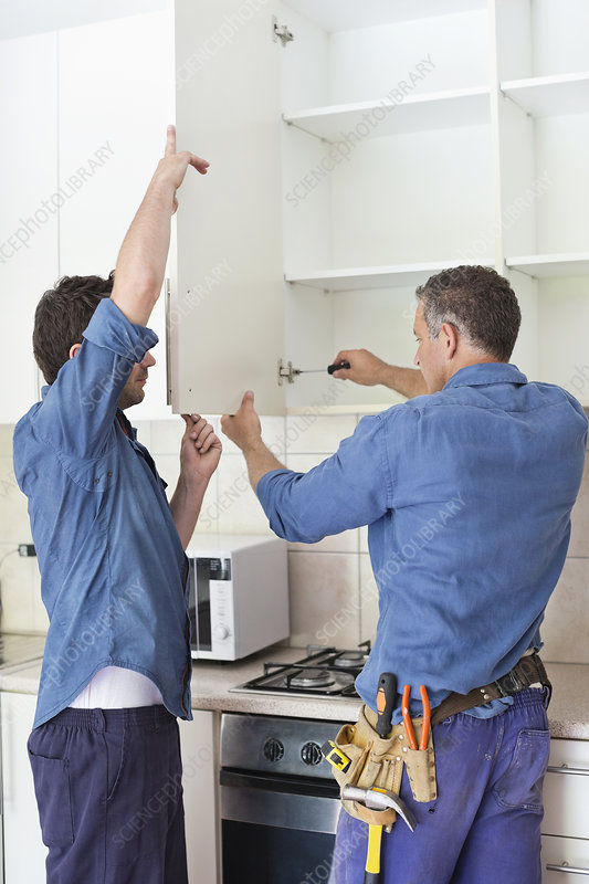 Workers installing cabinets in kitchen