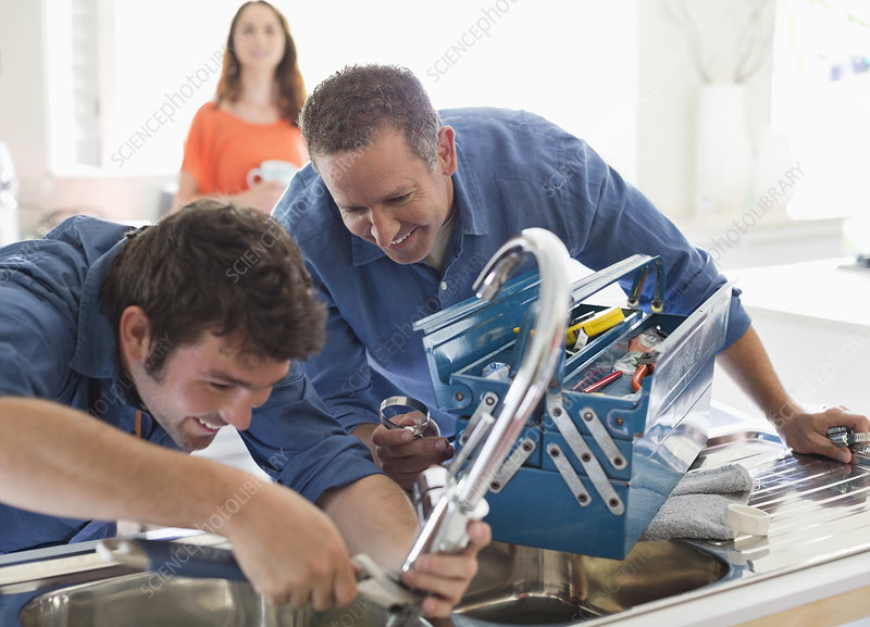 Plumbers working on kitchen sink