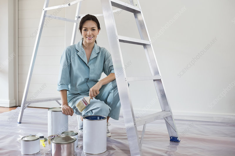 Smiling woman painting room