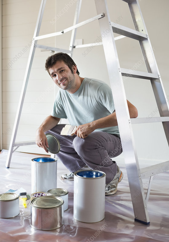 Man examining paint cans in room