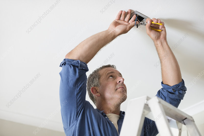 Electrician working on ceiling lights