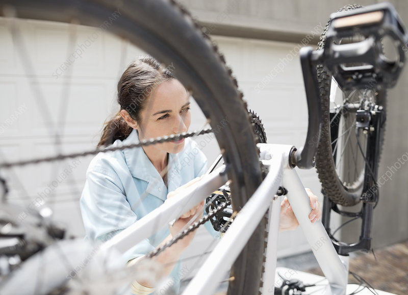 Woman working on bicycle in driveway