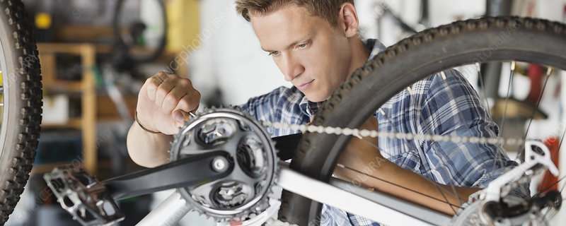 Man working on bicycle in shop