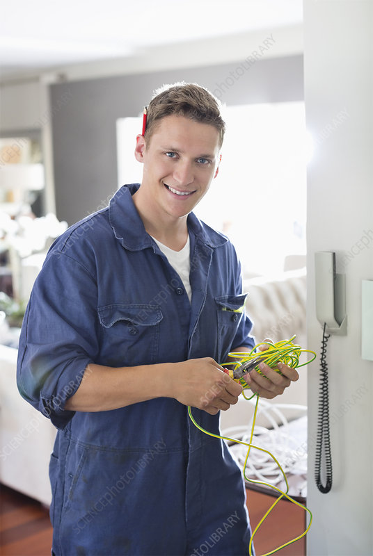 Electrician working on telephone in home