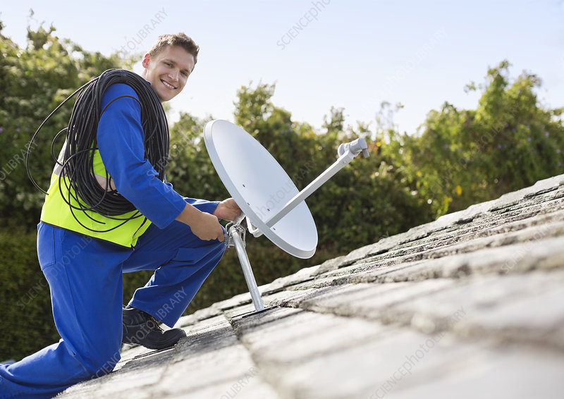 Worker installing satellite dish on roof