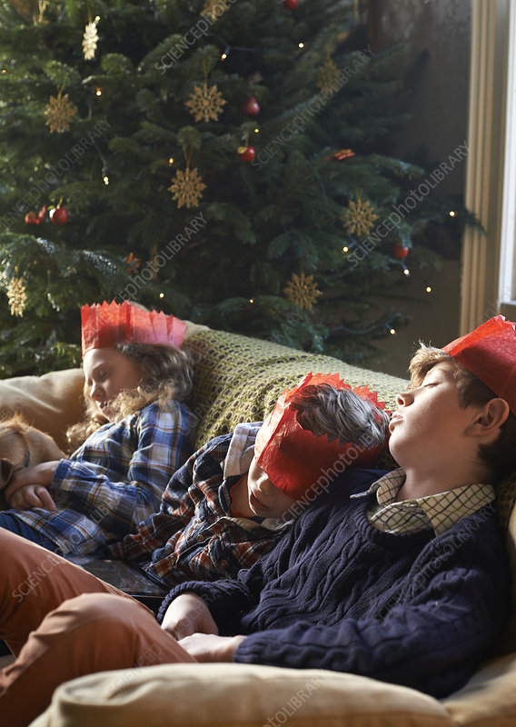 Children in paper crowns sleeping on sofa