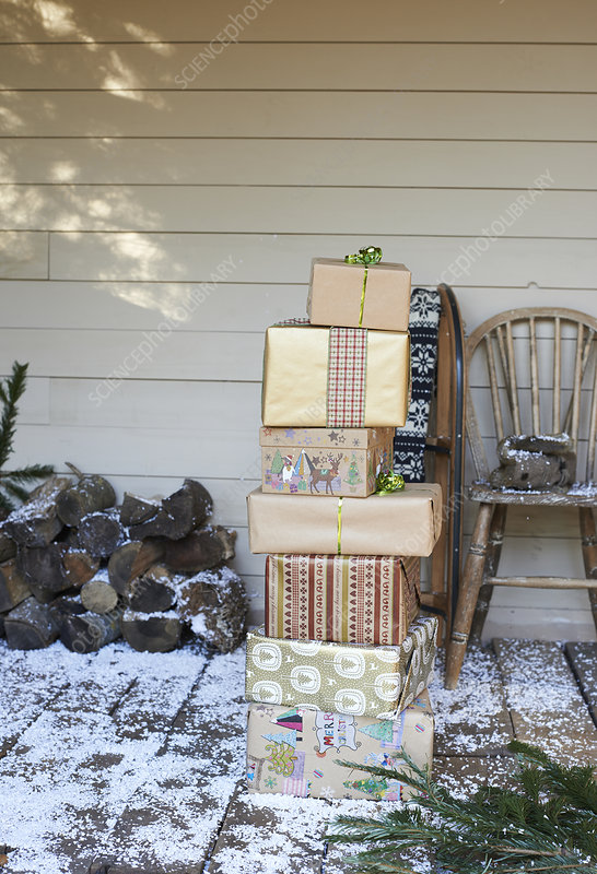 Stack of Christmas gifts on snowy patio